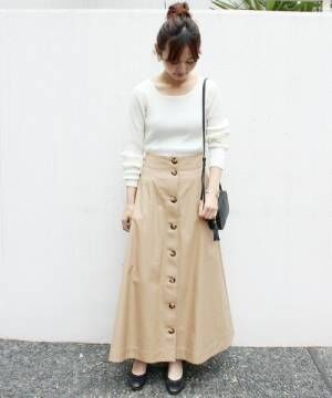 白ニットにベージュの前ボタンスカートを履いた女性