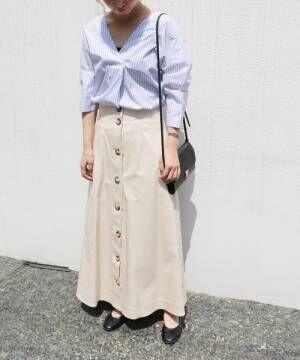 ストライプブラウスにベージュのフレアスカートを履いた女性
