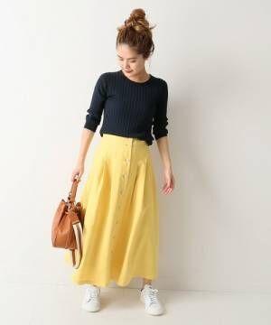 ネイビーのリブトップスに黄色のフレアスカートを履いた女性