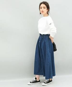 白のトップスにデニムフレアスカートを履いた女性
