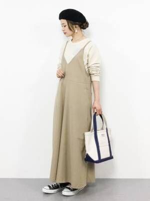 白のトップスにベージュのサロペットを着た女性
