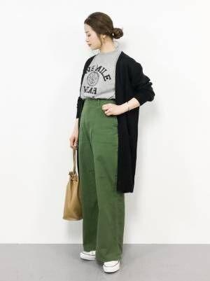 グレーのロゴT、グリーンのチノパンに黒のカーディガンを着た女性