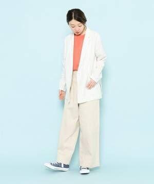 オレンジのトップス、アイボリーのパンツに白のジャケットを着た女性