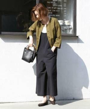 黒のサロペットにカーキのノーカラージャケットを着た女性