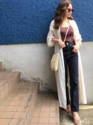 ブラウンのキャミソール、デニムパンツに白のリネンガウンを着た女性