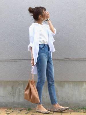 白T、デニムパンツに白シャツを着た女性