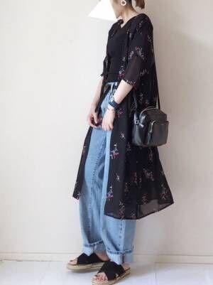 黒のトップス、デニムパンツに黒の花柄ガウンを着た女性