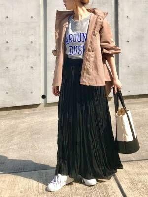 グレーのロゴスウェットに黒のワッシャープリーツスカート、キャメルのフードブルゾンを羽織ったコーデ
