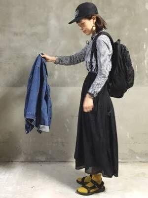 ギンガムチェックのシャツに黒のスカートを履いた女性