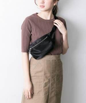 ブラウンのリブカットソーにベージュのスカート、黒のウエストバッグを合わせたコーデ
