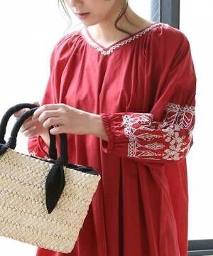 赤の刺繍ワンピースにかごバッグを持った女性