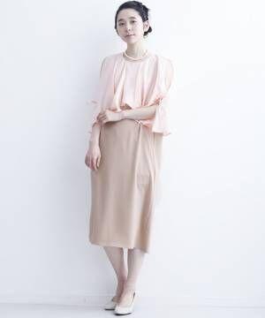 ピンクのオープンショルダーのワンピを着た女性