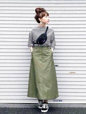 ボーダートップスにカーキのスカートを合わせて、お団子ヘアにした女性
