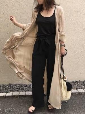 黒のタンクトップ、黒のワイドパンツにベージュのガウンを着た女性