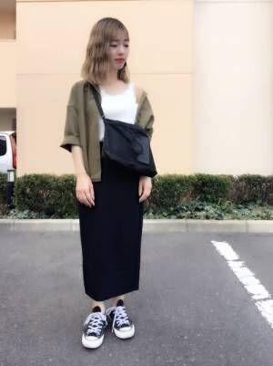 白のレースタンク、黒のタイトスカートにカーキのシャツを着た女性