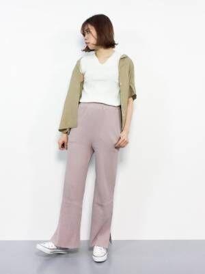 白のトップス、ピンクのニットパンツにベージュのシャツを羽織った女性
