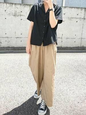 黒のシャツにベージュのワイドパンツを履いた女性
