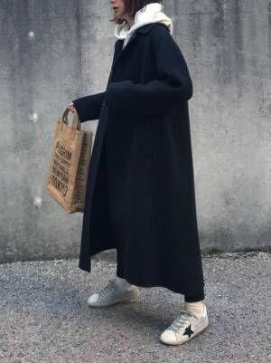 白パーカーに黒スキニーを合わせて、黒のステンカラーコートを羽織った女性