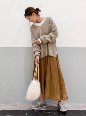 ベージュのニットに白のインナーを入れて、キャメルのプリーツスカートを合わせた女性