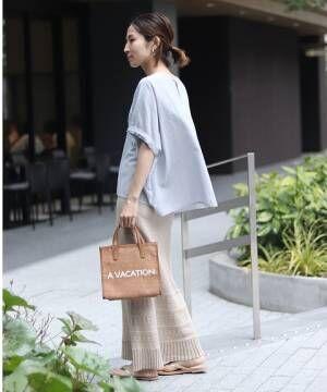 サックスブルーのブラウスにベージュの編み柄ニットスカートを合わせた女性