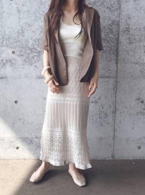 ベージュのタンクトップにオフホワイトの編み柄ニットスカートを合わせて、ブラウンのシャツを羽織った女性
