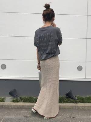 黒のバックプリントTシャツに透かし編みのニットスカートを合わせた女性