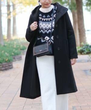 柄ニットに黒のフード付きコート、白のパンツを合わせたコーデ