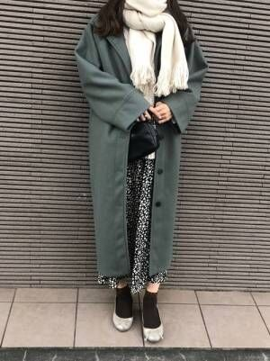 白のマフラーにグリーン系のコート、バレエシューズを合わせたコーデ