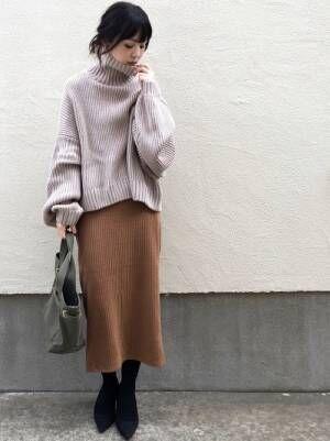 ライトブラウンのタートルニットにキャメルのリブニットスカートを合わせた女性