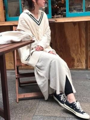 白のシャツワンピに黒のレギンスを合わせて、白のチルデンベストをレイヤードした女性