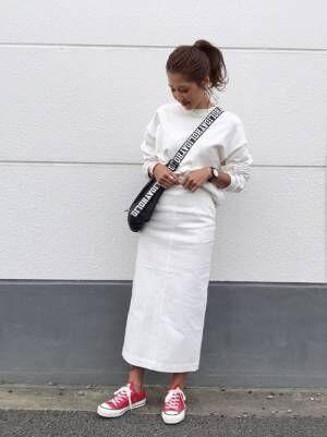 白のスウェットに白のタイトスカートを合わせて、赤のコンバースを差し色にした女性