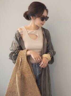 ベージュの変形タンクトップにデニムパンツを合わせて、カーキのガウンを羽織った女性