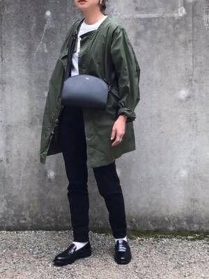 白Tに黒スキニーを合わせてミリタリージャケットを羽織り、黒のレザーバッグとローファーを合わせた女性