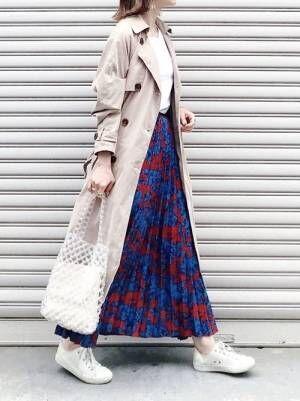 白Tにブルーに赤の花柄が入ったスカートを合わせて、トレンチコートを羽織った女性