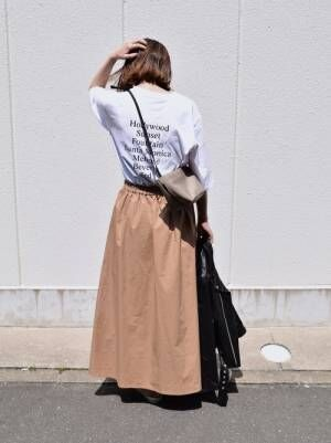 白のバックプリントTシャツにベージュのフレアスカートを合わせた女性