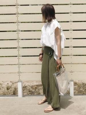 白いシャツにカーキのラップパンツにTKEESのサンダルにクリアバッグを持つ女性