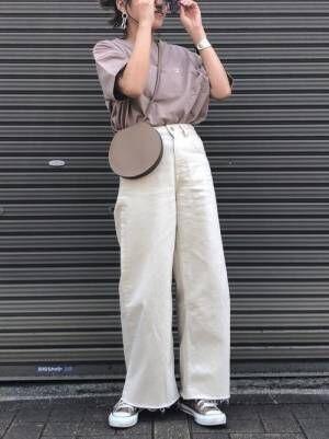 チャンピオンにTシャツに白いワイドデニムにベージュコンバースを履く女性