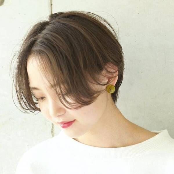 頰ラインまである長めの前髪のハンサムショートヘアの女性
