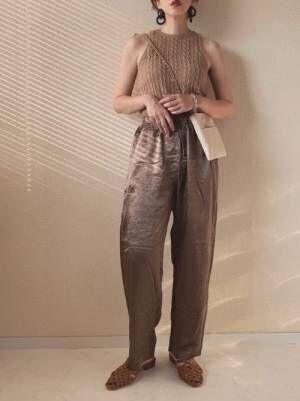 ベージュのサマーニットノースリーブにブラウンのサテンパンツを履く女性