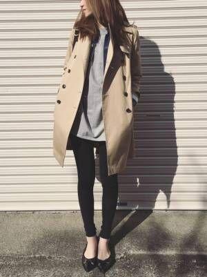 トレンチコートにグレーパーカー、黒スキニーを着用する女性