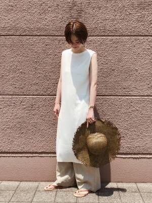 白いノースリーブワンピースにワイドパンツを履いて麦わら帽子を持つ女性