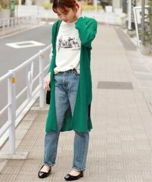 白のプリントTシャツにデニムを合わせて、グリーンのロングカーデを羽織った女性