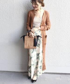 ベージュのトップスにボタニカル柄のパンツを合わせて、ブラウンのロングカーデを羽織った女性