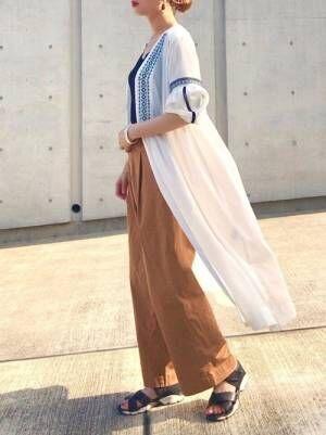 黒のタンクトップにベージュのパンツを合わせて、白にブルーの単色刺繍が入ったワンピースを羽織った女性