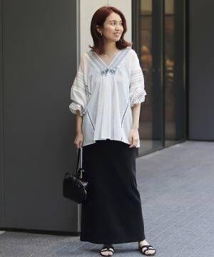白に黒のスモッキング刺繍をほどこしたコットンブラウスに黒のタイトスカートを合わせた女性