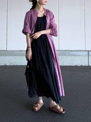 ピンクのシャーリングシャツにノースリーブ黒ワンピースにビリケンを履く女性
