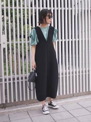 カーキのTシャツにブラックのオールインワンにブラックのレザーバッグを持つ女性