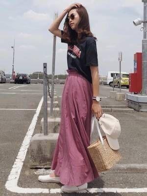 黒のロゴTシャツにピンクのシャーリングスカートを履いてポーズをとる女性