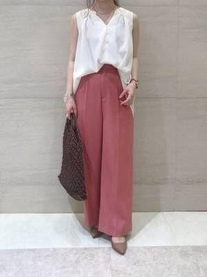 白いノースリーブシャツにピンクのセンタープレスパンツにパンプスを履く女性