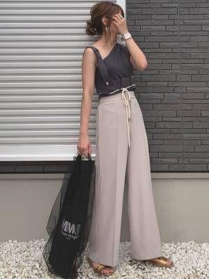 アメリのブラックカットソーにくすみピンクのセンタープレスパンツを履く女性